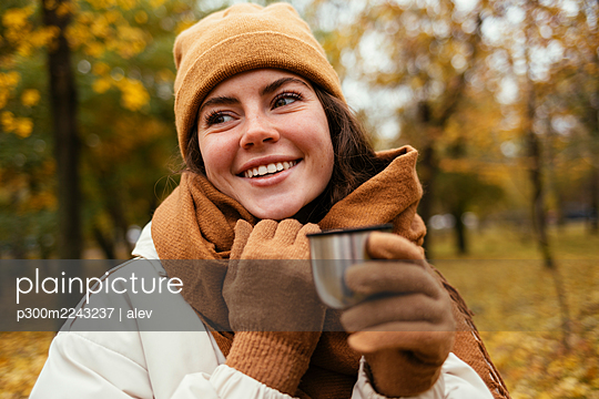 Happy young woman looking away while holding insulated cup in autumn park - p300m2243237 by alev