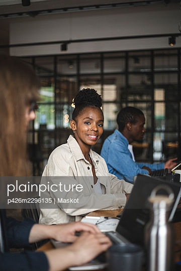 Portrait of smiling female hacker in office - p426m2296135 by Maskot