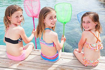 Drei Mädchen sitzen mit Catcher am Wasser - p045m1591423 von Jasmin Sander