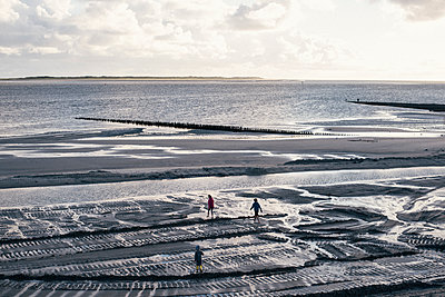 Children playing in the North Sea at low tide - p1046m1467532 by Moritz Küstner