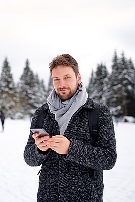 Man using smartphone in snow-capped landscape - p1124m1589298 by Willing-Holtz