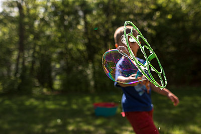 Boy blowing bubble using bubble wand in yard - p1166m1489426 by Cavan Images