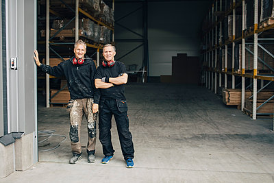 Full length portrait of confident workers standing in entrance at industry - p426m1537029 by Maskot