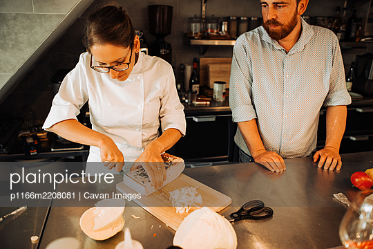 Female chef in uniform working at restaurant kitchen with assistant - p1166m2208081 by Cavan Images