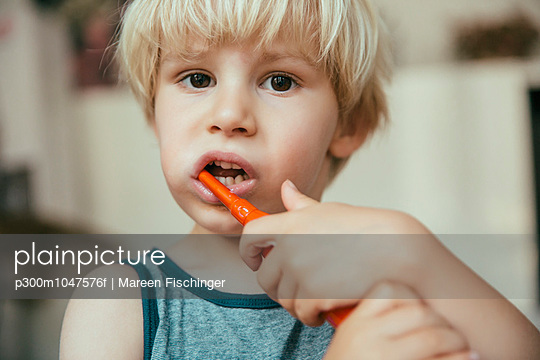 Portrait of little boy brushing his teeth with an electric toothbrush - p300m1047576f by Mareen Fischinger