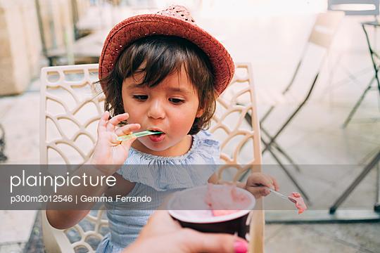 Cute toddler girl eating an ice cream held by her mother - p300m2012546 von Gemma Ferrando