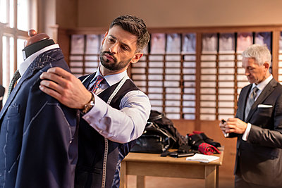 Tailor adjusting suit on dressmakers model in menswear shop - p1023m1173665 by Rafal Rodzoch