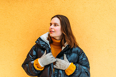 Young woman  while standing against yellow wall - p1166m2153381 by Cavan Images