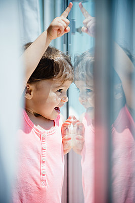 Mixed race girl looking out window - p555m1479067 by JGI/Jamie Grill