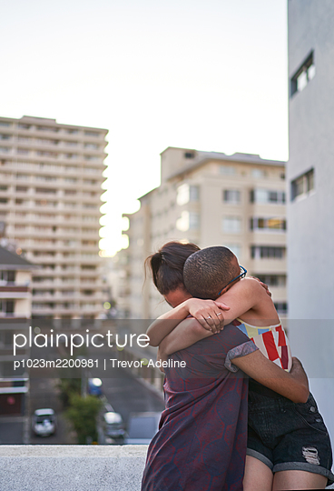 Happy young couple hugging on urban balcony - p1023m2200981 by Trevor Adeline