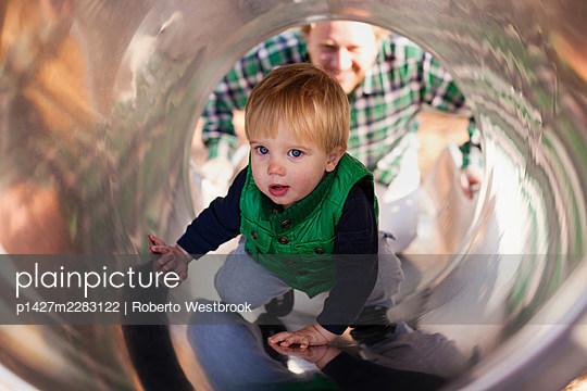 Boy climbing up slide in playground - p1427m2283122 by Roberto Westbrook