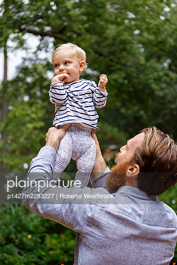 Father holding baby girl in air, outdoors - p1427m2283227 by Roberto Westbrook
