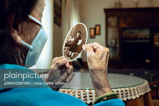 Senior woman remembering childhood memories at home - p300m2287666 by Jose Carlos Ichiro