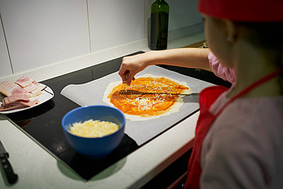 The girl with the red chef's hat adds the cheese to the pizza dough - p1166m2201420 by Cavan Images