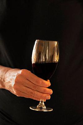 Hand hält ein Glas Rotwein - p1418m2175248 von Jan Håkan Dahlström