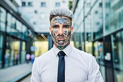 Young businessman with tattooed face, portrait - p300m1587824 von Zeljko Dangubic
