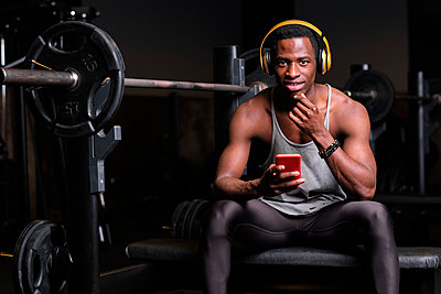 Young man with headphones using smart phone at gym - p300m2273622 by Antonio Ovejero Diaz