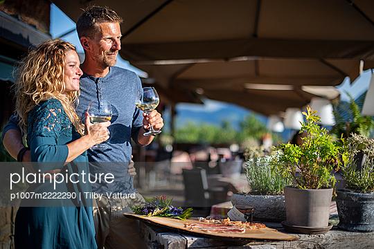 Junges Paar trinkt Weißwein auf der Terrasse eines Restaurants - p1007m2222290 von Tilby Vattard