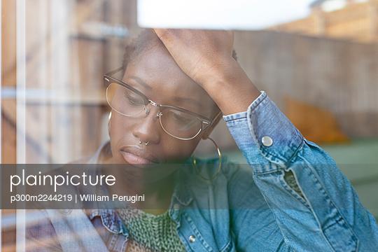 Sad woman looking through window - p300m2244219 by William Perugini