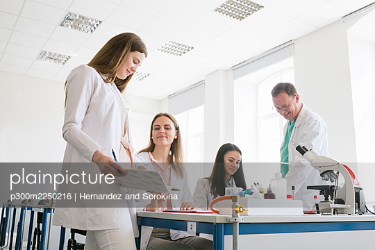 Students and teacher in white coats discussing in science class - p300m2250216 by Hernandez and Sorokina