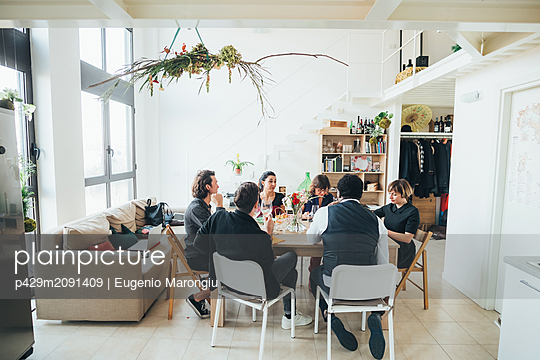 Businessmen and businesswomen celebrating at lunch party in loft office - p429m2091409 by Eugenio Marongiu