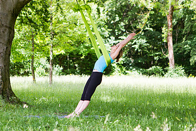 Young woman does stretching exercises with rubber band, Munich, Bavaria, Germany - p1026m996445f by Patrick Frost