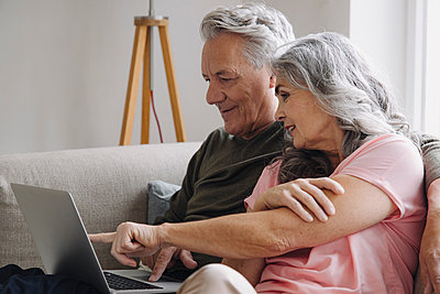 Senior couple with laptop relaxing on couch at home - p300m2156265 by Gustafsson