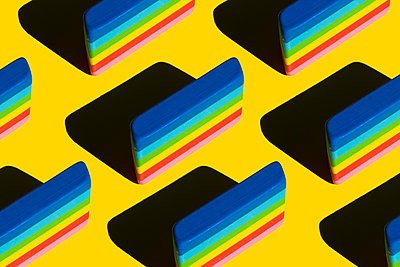 Pattern of rainbow colored erasers against yellow background - p300m2199667 by Xavier Lorenzo