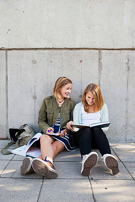 Two teenage girls sitting on pavement - p312m695672 by Susanne Walstrom
