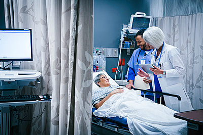Doctor and nurse talking with patient in hospital bed - p555m1521521 by FS Productions