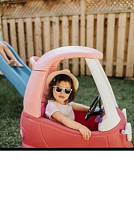 Toddler riding toy car in backyard - p924m2153109 by Sara Monika