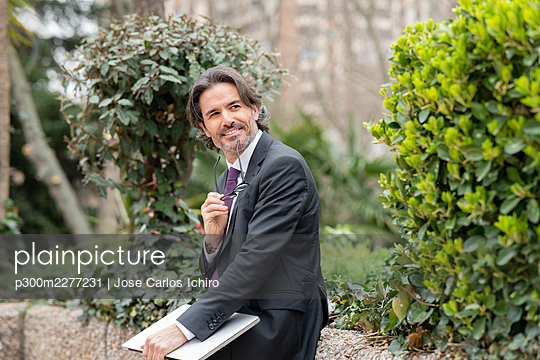 Smiling businessman with laptop looking away while sitting on retaining wall in office park - p300m2277231 by Jose Carlos Ichiro