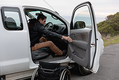 Disabled man getting out of a car into a wheelchair - p1315m2131529 by Wavebreak