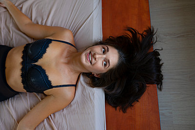 Woman in bra lying on bed - p1646m2247714 by Slava Chistyakov