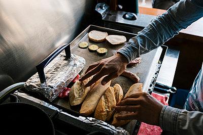 Chef grilling bread on griddle at restaurant - p300m2275133 by Ezequiel Giménez