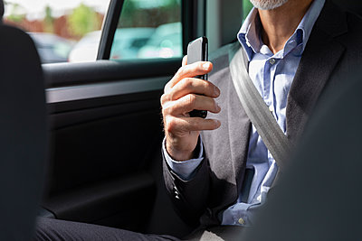 Businessman holding smart phone in car - p300m2287632 by Emma Innocenti