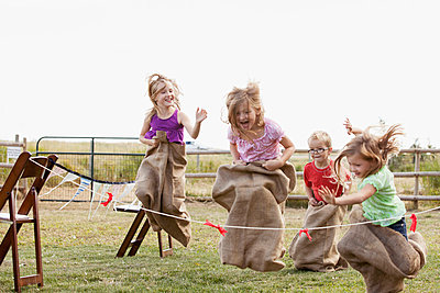 Cousins competing in potato sack race. - p328m784043f by Hero Images