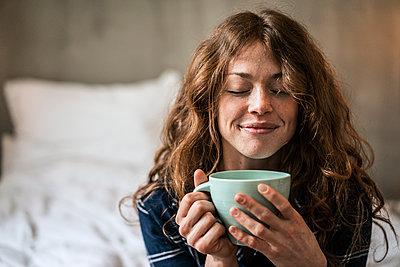 Junge Frau mit Kaffeebecher im Schlafzimmer - p586m1144027 von Kniel Synnatzschke