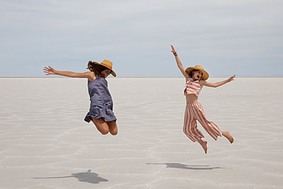 Two girls are jumping with joy in the desert - p756m2217340 by Bénédicte Lassalle