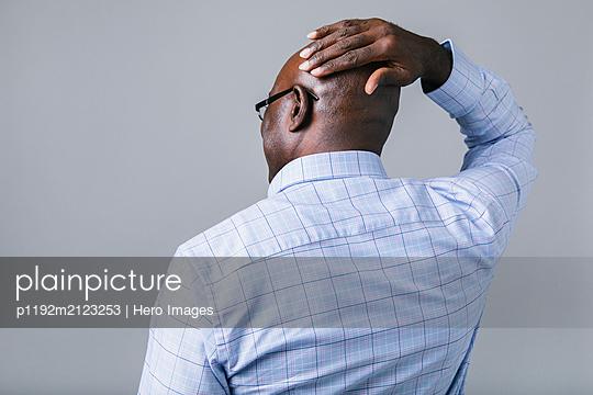 Businessman rubbing bald head - p1192m2123253 by Hero Images
