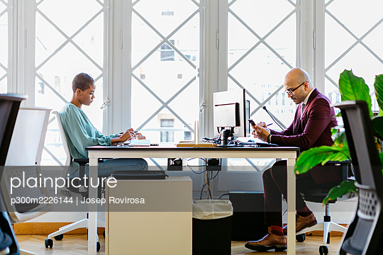 Business professionals working at desk against window in office - p300m2226144 by Josep Rovirosa