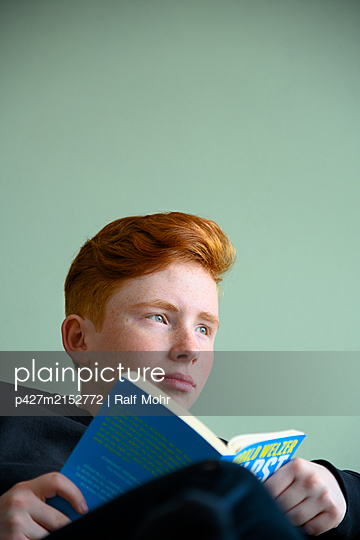 Red-haired girl reading a book - p427m2152772 by Ralf Mohr