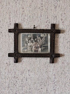 Old group photo in a carved frame on the wall - p1383m2148384 by Wolfgang Steiner