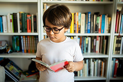 Portrait of serious boy with glasses standing in front of book shelves reading a comic - p300m2167570 by Valentina Barreto