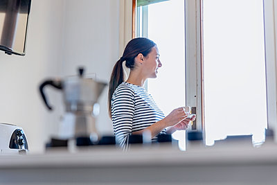 Young woman having breakfast coffee in the kitchen; Florence, Italy - p300m2287511 von Emma Innocenti