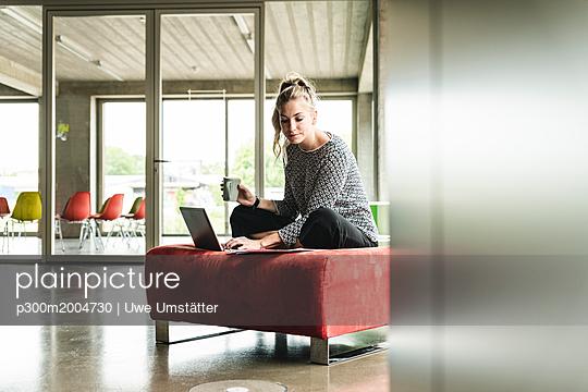 young businesswoman working in modern office, sitting on stool, using laptop - p300m2004730 von Uwe Umstätter