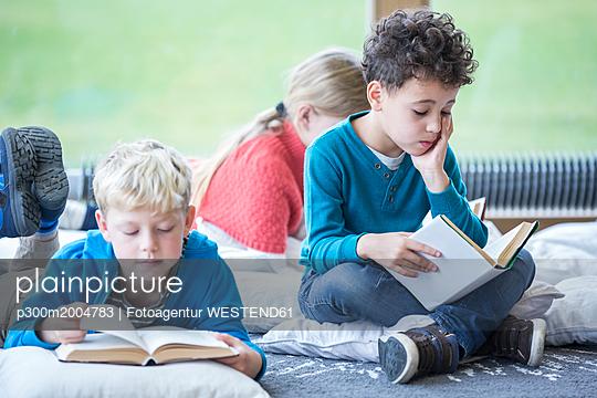 Pupils reading books on the floor in school break room - p300m2004783 von Fotoagentur WESTEND61