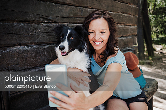 Smiling woman taking selfie with pet dog through smart phone while sitting outside cottage in forest - p300m2293418 by Eva Blanco
