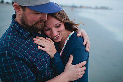 Happy couple embracing while standing at beach - p1166m1210267 by Cavan Images