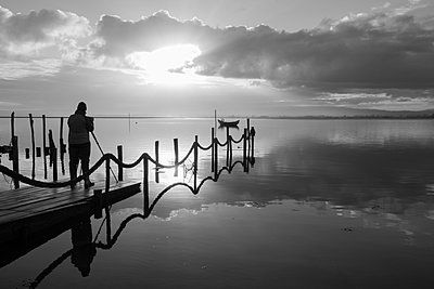 Photographer shooting the wooden boat at sunrise - p1166m2152244 by Cavan Images